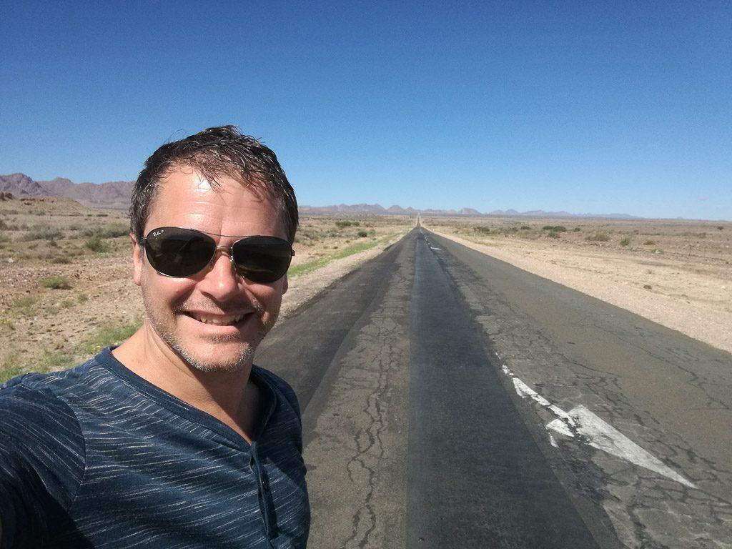 Thomas an einer endlos geraden Straße in Namibia